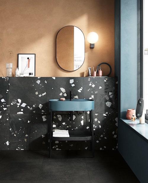 point d'eau bleu devant un mur noir avec incrustations blanches et grises