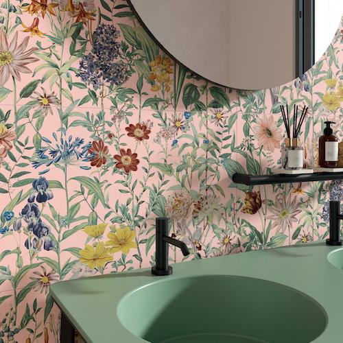lavabo vert devant un mur au carrelage fleuri